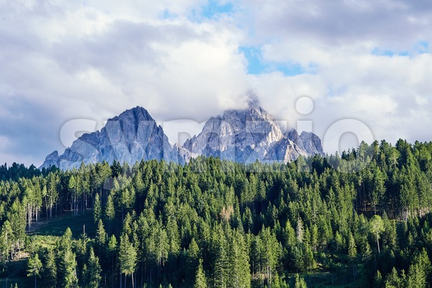 Dolomites mountains in the warm season. Green forest on foreground. Province of Belluno, Italy Stock Photo