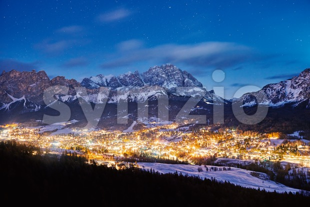 Cortina Ampezzo ski resort city at night. Mountains covered in snow on background. Province of Belluno, Italy Stock Photo
