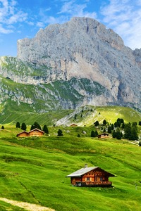 Seceda mountain with blue grass and wooden cottages on foreground. Italy beauties Stock Photo