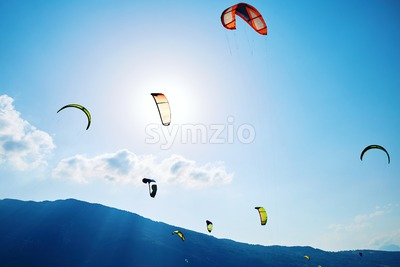 Colorful paragliding formation above Santa Croce Lake. Belluno, Italy Stock Photo