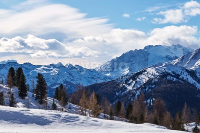 Dolomite mountains covered in snow at daylight. Blue sky with clouds. Belluno, Italy Stock Photo