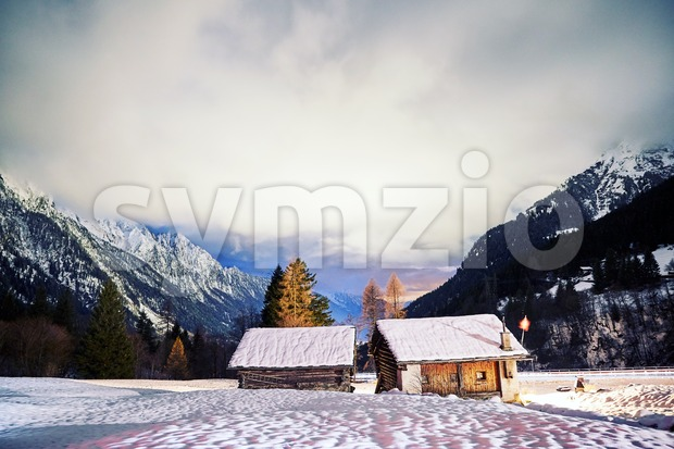 Long exposure swiss mountains at night. Wooden houses in foreground Stock Photo