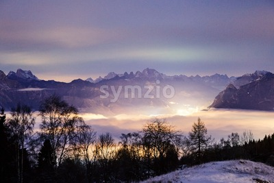 Dolomite mountains covered in snow at sunset. Long exposure. Cloud carpet on background. Belluno, Italy Stock Photo