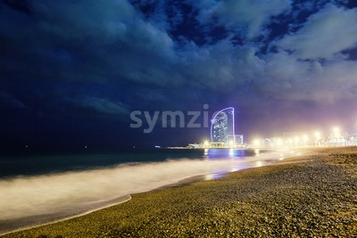 Long exposure Barcelona beach coastline at night. Futuristic hotel on background. Spain Stock Photo