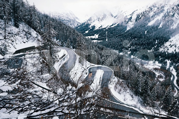 Curved road in the mountains covered in snow. Switzerland Stock Photo