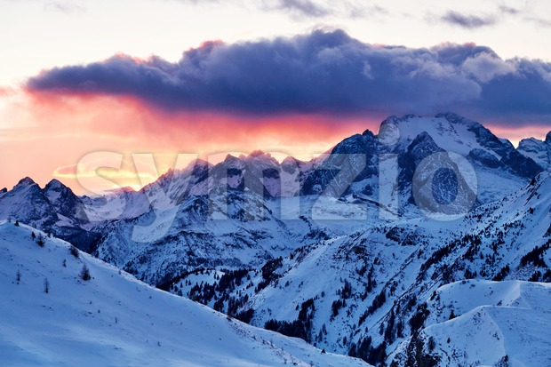 Marmolada mountain peak covered in snow at sunset. Hot red sun. Italy Stock Photo