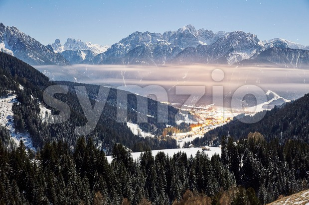 Toblach at sunset with clouds and mountains covered in snow. Italy