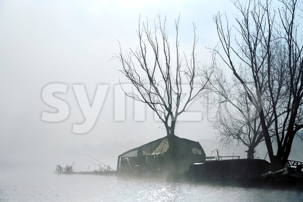 Dark island of fishermen in autumn season. Fog. Trees growing. Close up Stock Photo