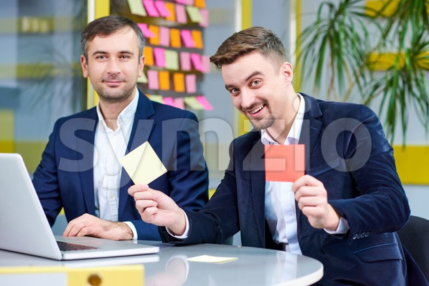Two mature caucasian male having fun in the office with stickers. Wearing formal clothes. Stock Photo