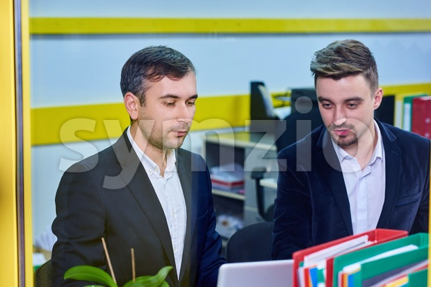 Two mature caucasian male working in the office, discussing a project on laptop. Wearing formal clothes. View through windo Stock Photo
