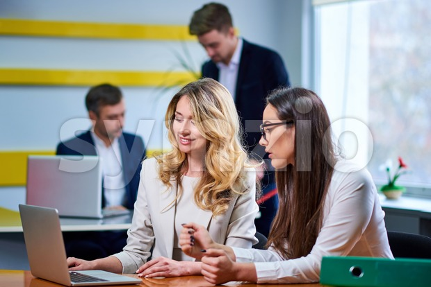 Caucasian mature women ladies at meeting table discussing a business plan with laptop computer in office. Workers on background Stock Photo