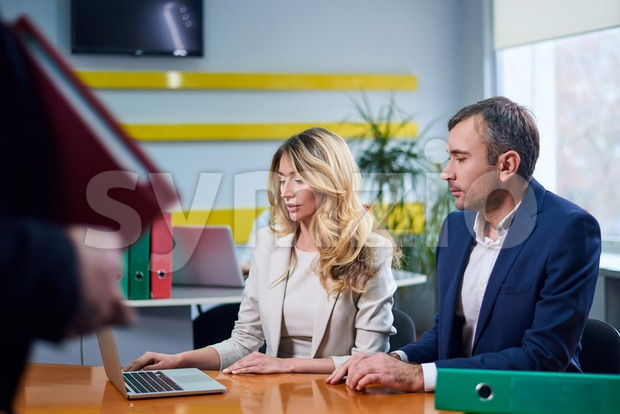 Caucasian mature man and woman at meeting table discussing a business plan with laptop computer in office. Workers on background Stock Photo