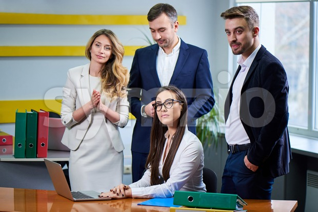 Team of caucasian mature women and men at meeting table discussing a business plan with laptop computer in office