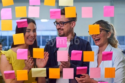 Two caucasian mature women and a man discussing ideas on stickers in the office. View through window Stock Photo