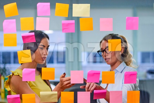 Two caucasian mature women discussing ideas on stickers in the office. View through window Stock Photo