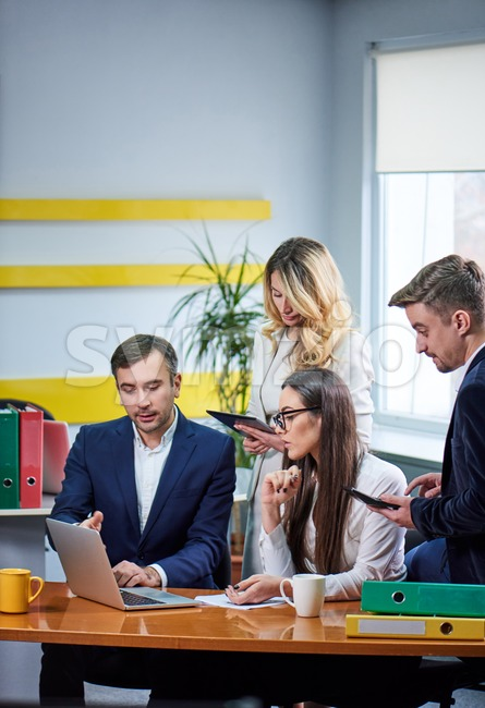 Team of caucasian mature women and men at meeting table discussing a business plan with laptop computer in office Stock Photo