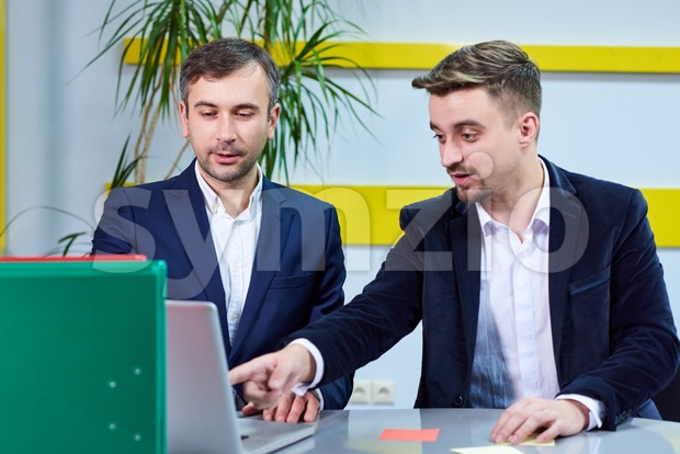 Two mature caucasian male working in the office, discussing a project on laptop. Wearing formal clothes Stock Photo