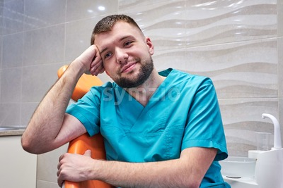 Bored male dentist sitting in the chair in dental cabinet Stock Photo