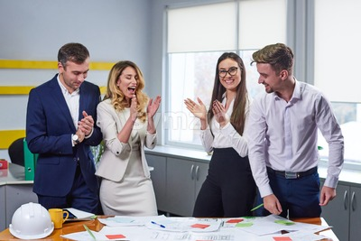 Team of caucasian mature women and men at meeting table discussing a business plan pointing at laptop computer in office. Stock Photo