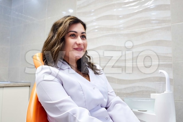 Young female dentist sitting on the chair in dental cabinet and smiling Stock Photo