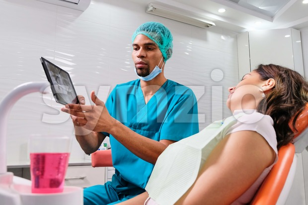 African male dentist explaining x-ray to the patient sitting in the chair