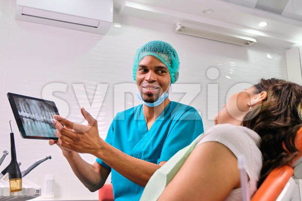 African male dentist explaining x-ray to the patient sitting in the chair Stock Photo