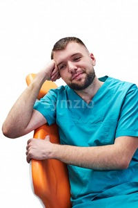 Bored male dentist sitting in the chair in dental cabinet. Isolated background Stock Photo