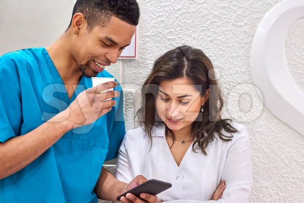 Young male african and female caucasian dentists on coffee break. Smiling and showing stuff on the smartphone