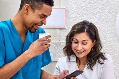 Young male african and female caucasian dentists on coffee break. Smiling and showing stuff on the smartphone Stock Photo