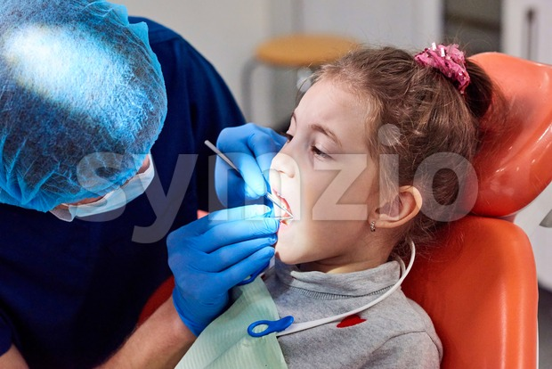 Male dentist examining little girl's teeth. Bright light glowing into the mouth Stock Photo