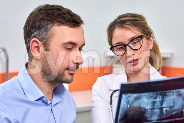 Caucasian female dentist explaining to male patient the x-ray in dental cabinet