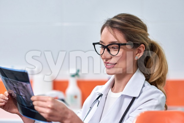 Caucasian blonde female dentist analyzing the x-ray in dental cabinet Stock Photo