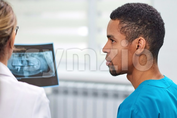 Caucasian female dentist explaining to african male rookie how to analyze the x-ray