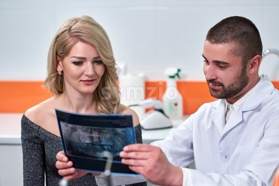 Caucasian male dentist explaining to female patient the x-ray in dental cabinet Stock Photo