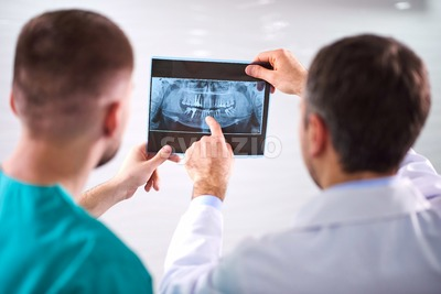 Two caucasian male dentists analyzing x-ray in dental cabinet. Close-up shot Stock Photo