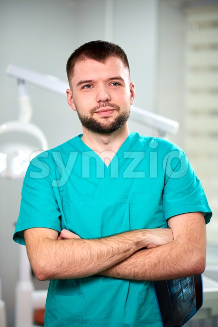 Caucasian male dentist holding xray in hands and smiling. Looking towards camera Stock Photo