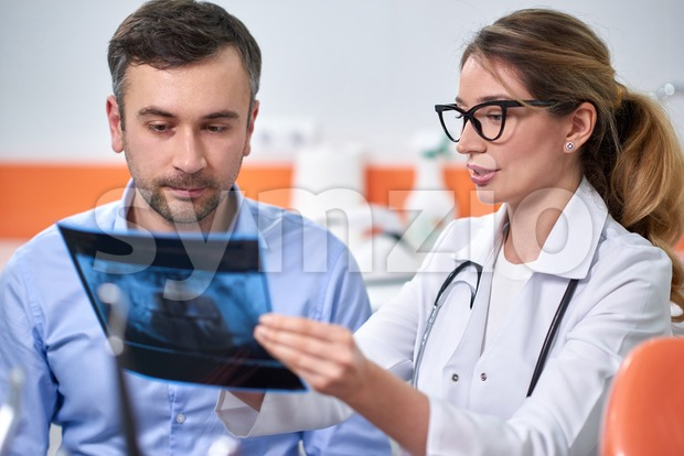 Caucasian female dentist explaining to male patient the x-ray in dental cabinet Stock Photo