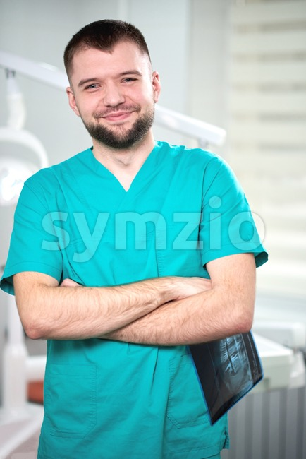 Caucasian male dentist holding xray in hands and smiling. Looking towards camera