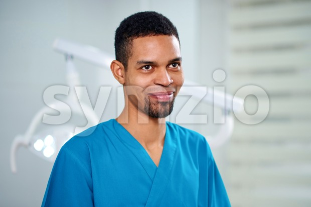 African male dentist looking towards camera and smiling. Equipment on background Stock Photo