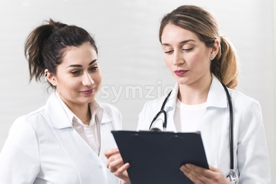 Two female assistants dressed in white coats talking to each other in the dentistry center. White and blured background. Healthcare idea Stock Photo