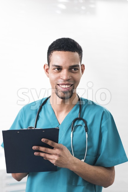 Men in a cyan colored dental coat taking notes. Serious looking person infront of a white background. Stetoscope on the neck. Healthcare idea Stock Photo
