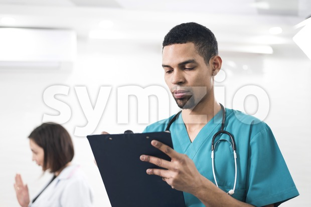 Men in a cyan colored dental coat taking notes. Serious looking person infront of a white background. Stetoscope on the ...