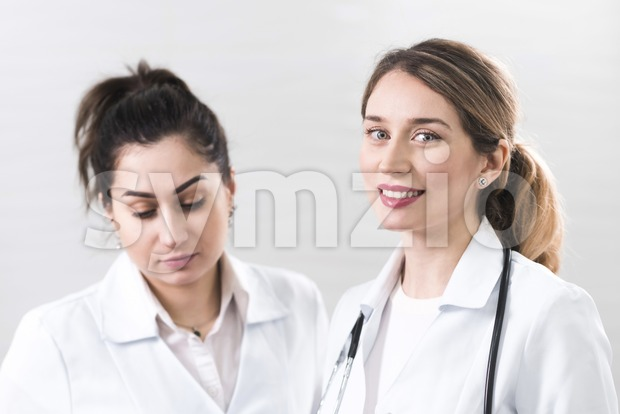 Two female assistants dressed in white coats talking to each other in the dentistry center. White and blured background. Healthcare idea. Smiling Stock Photo