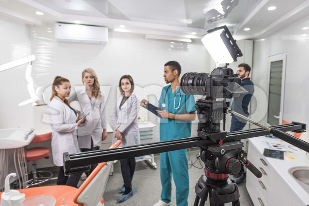 Group of filmmakers shooting a movie in a dentistry. Small set with bright lights, a slider and a camera. Five people in the room Stock Photo