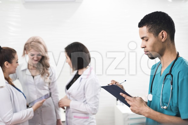 Men in a cyan colored dental coat taking notes. Serious looking person infront of a white background with some female ...