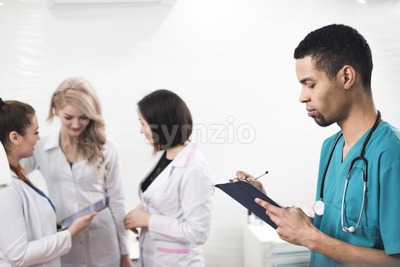 Men in a cyan colored dental coat taking notes. Serious looking person infront of a white background with some female assistants. Stetoscope on the Stock Photo