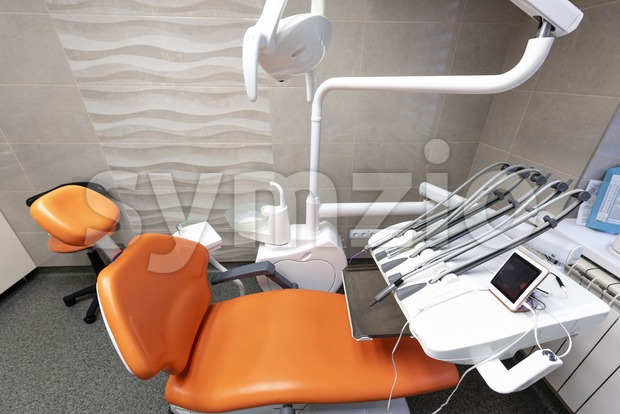 Dentistry tools in a bright lit cabinet. Modern looking place with comfort in mind. Orange chair in the foreground. Dental health idea Stock Photo